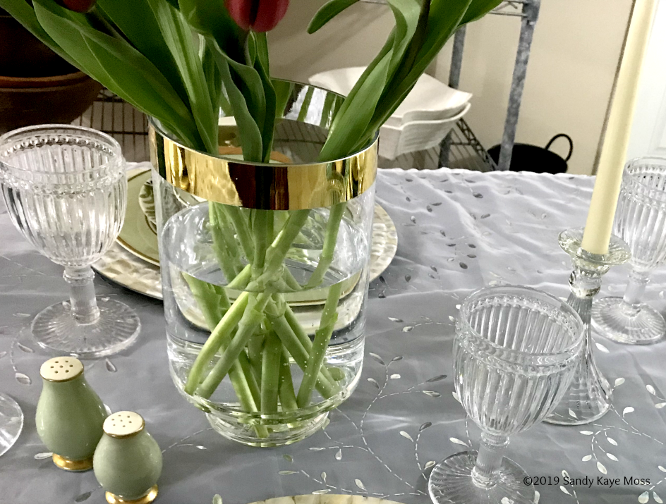 vase with gold rim and tulips, stemware, salt and pepper containers, candle and candle holder